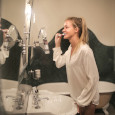 Young blond woman brushing her teeth in front of the mirror