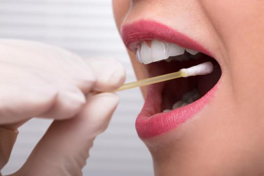 Cotton swab being put inside a woman's mouth